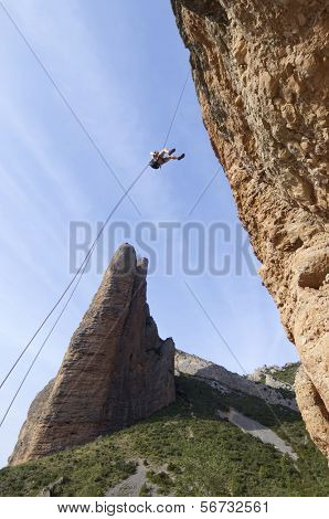 climber descending with the technique of rappelling in Riglos mountains