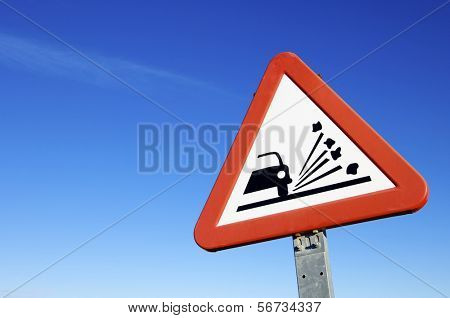 road sign that warns of the danger of  loose gravel on the  road