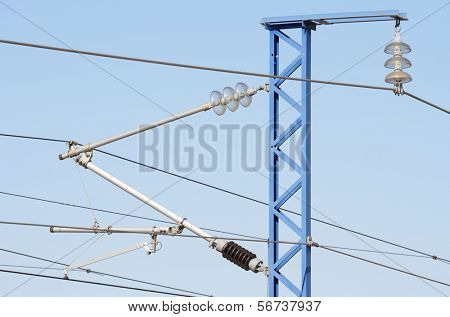 forefront of a railway catenary  with a blue sky