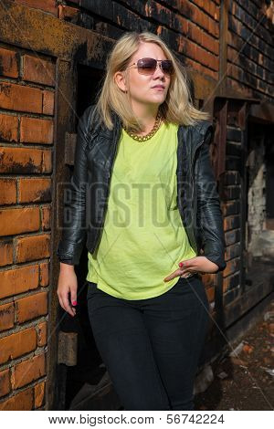 Trendy Blond Girl Leaning Against A Brick Wall
