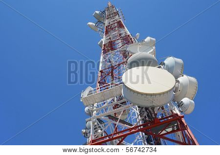 bottom view of  a telecommunications tower with a clear blue sky