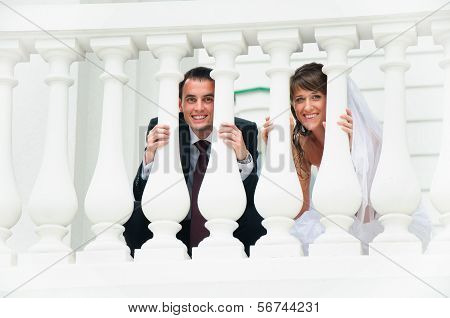Wedding Couple Smile And Look Out From White Baluster