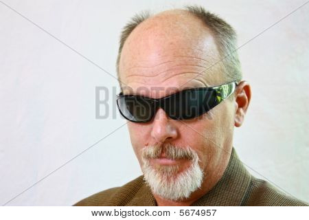Man With Sunglasses And Slight Smirk On His Face.