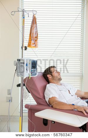 Male patient sleeping while receiving chemotherapy in hospital room