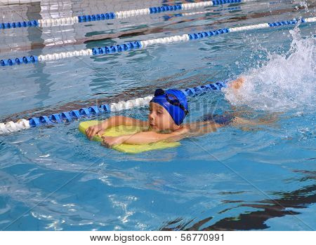 Child 7 Years Boy Learning To Swim In Lap Pool.