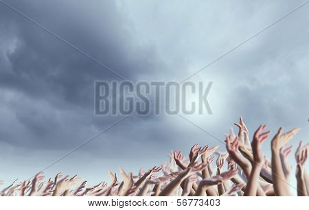 Crowd of people with hands raised up in to sky