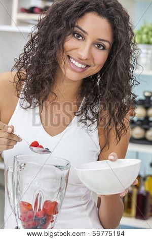 A beautiful happy young woman or girl making a fresh fruit smoothie in her kitchen at home