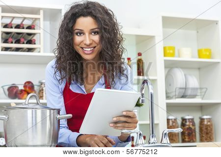 A beautiful happy young woman or girl wearing a red apron & using a tablet computer while cooking in her kitchen at home