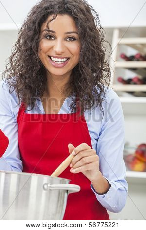 A beautiful girl or young woman looking happy wearing red apron & cooking in her kitchen at home
