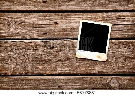 Blank instant photo frame on old wooden background.
