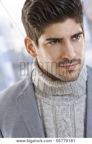 Closeup portrait of handsome young man in polo-neck sweater, looking away.
