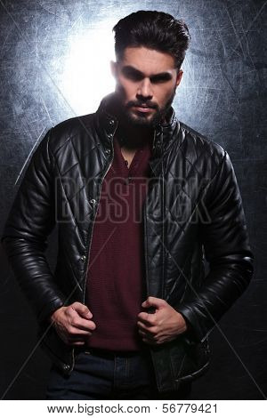 young fashion man with long beard pulling on his leather jacket and poses for the camera