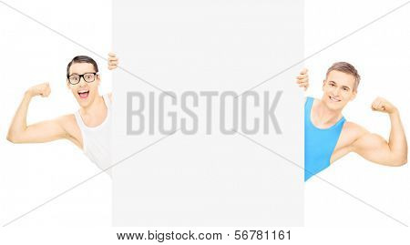 Nerdy guy and muscular athlete showing biceps and standing behind blank panel, isolated on white background, shot with a tilt and shift lens