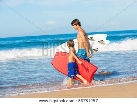 Father and Son Going Surfing Together on Tropical Beach in Hawaii