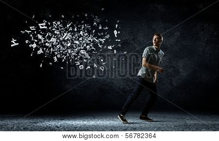 Funny image of young man trying to escape from flying letters