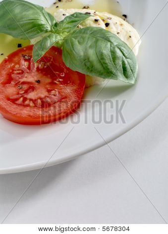 Mozzarella, Fresh Tomato Slice And Aromatic Basil Leaves With Olive Oil And Black Pepper On White Pl