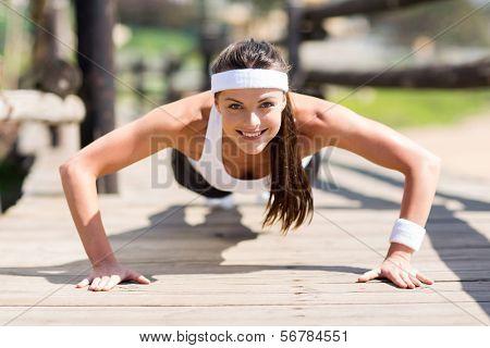 healthy young woman doing pushups outdoors