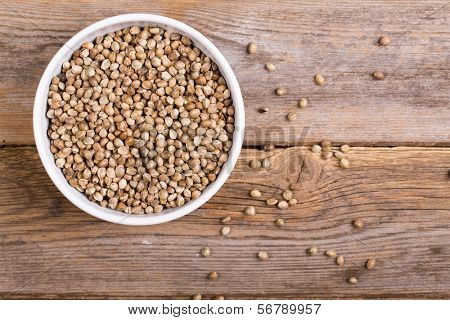 A white ceramic bowl full of hemp seeds over old wood background