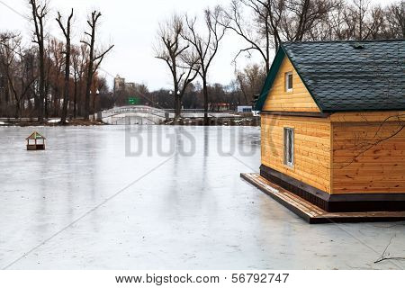 Frozen Lake With Bridge And Wooden House