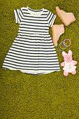 Beautiful dress and gumshoes for little girl on green carpet poster