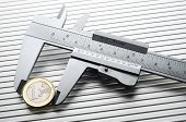 pic of vernier-caliper  - metal caliper measuring a one euro coin  on a metal surface - JPG