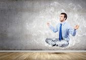 stock photo of holistic  - Young businessman sitting in lotus pose and meditating - JPG
