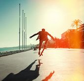 picture of skateboarding  - Silhouette of Skateboarder jumping in city on background of promenade and sea - JPG