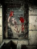 stock photo of grotesque  - Photo of a hungry zombie covered with blood at the window - JPG