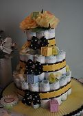 stock photo of three tier  - Gender neutral, baby shower white diaper cake with yellow, black & white ribbon.