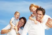 picture of happy family  - young happy family having fun outdoors dressed in white and with blue sky in background - JPG