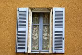 picture of lace-curtain  - Brown stone building with blue window shutters and lace curtain in France - JPG