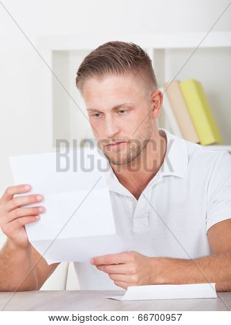 Man Sitting Reading A Letter With A Serious Expression
