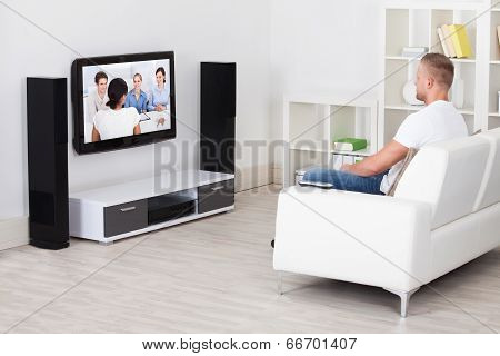 Man Sitting On A Sofa In His Living Room Watching Television