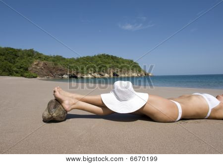 Bikini Lady Resting Beach Feet On Coconut With White Hat