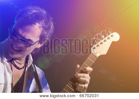 Male Guitarist Playing With Expression. Shot With Strobes And Halogen Light On Slow Shutter Speed