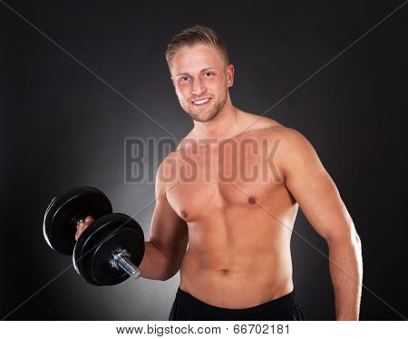 Young Man Working Out Lifting Weights In A Gym