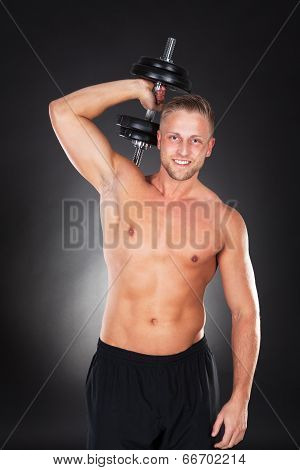 Muscular Fit Young Man Working Out With Weights