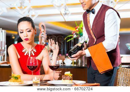 Waiter showing bottle of wine in restaurant