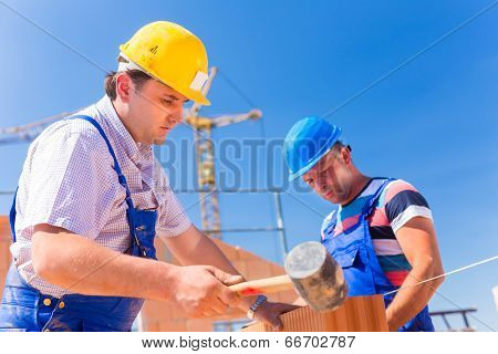 Construction site worker building a home or house doing bricklaying work on the walls of the shell