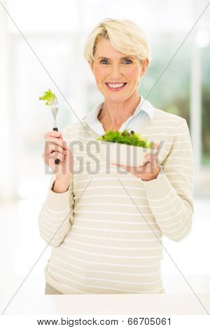 happy mid age woman eating green salad at home