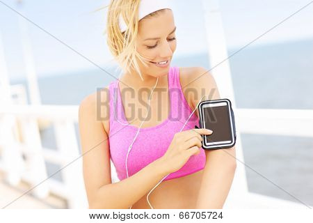 Young fit woman in pink sports bra touching phone on the pier over sea