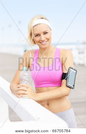 Young fit woman with water on the pier in pink sports bra and white band
