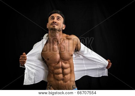 Male Bodybuilder Taking Off His Shirt Revealing Muscular Torso