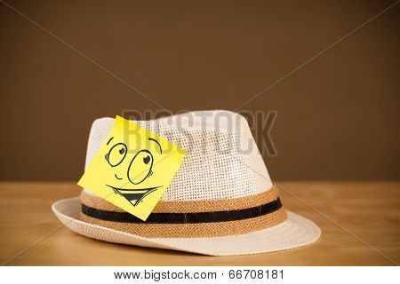 Drawn smiley face on a post-it note sticked on hat