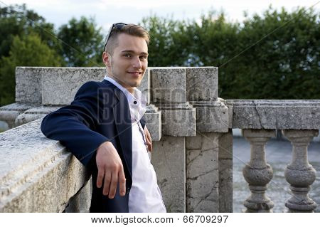 Handsome Blond Young Man On Marble Banister