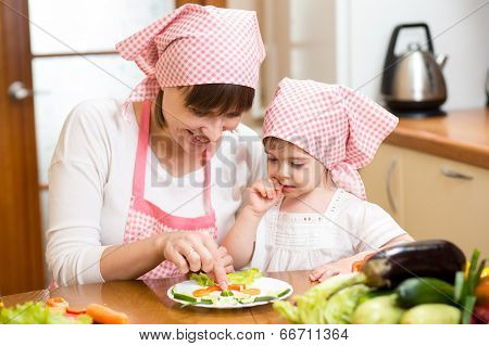 Mother And Kid Girl Making Funny Face From Vegetables On Plate