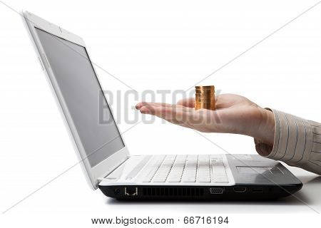 Man's Hand Holding A Stack Of Coins On A Laptop