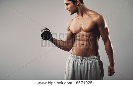 Young Muscular Man Exercising With Dumbbells