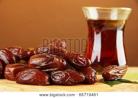 Dried dates with cup of tea on table on brown background