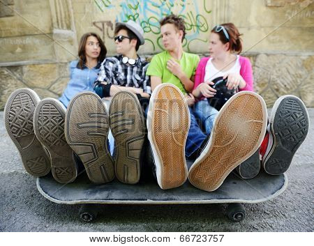 Urban stylish trendy young teenage people with legs on skate